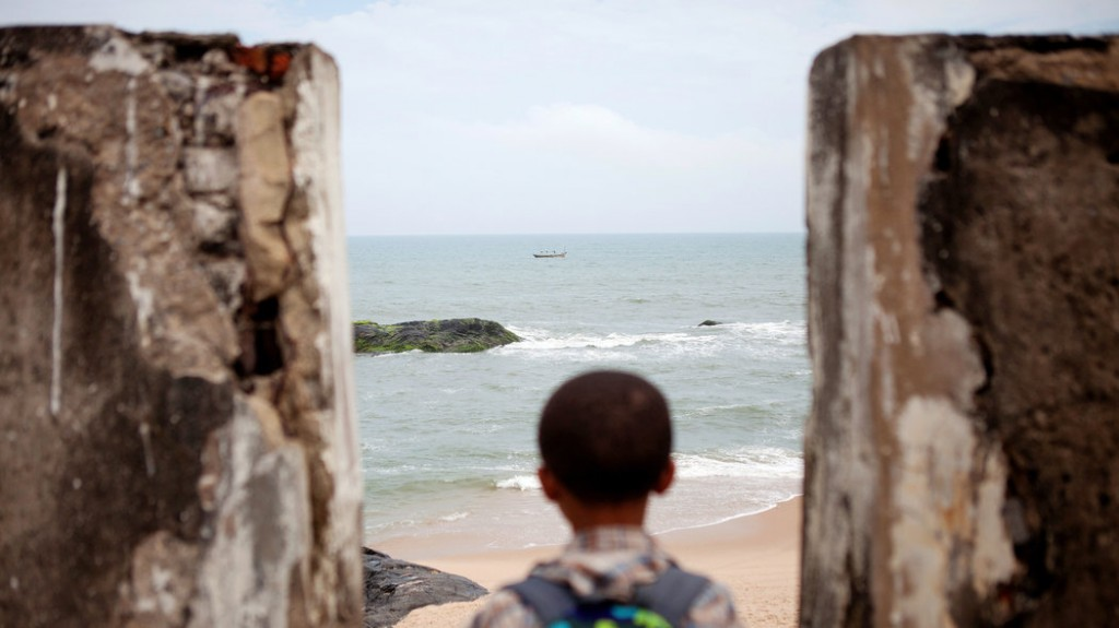 Jasir Robert Ryan-Lee, a descendant of Venture Smith, looks out to the shore from the roof of the fort in Anomabo, Ghana, where his ancestor was held as a slave, then taken to a ship through its Door of No Return. Credit Jane Hahn for The New York Times